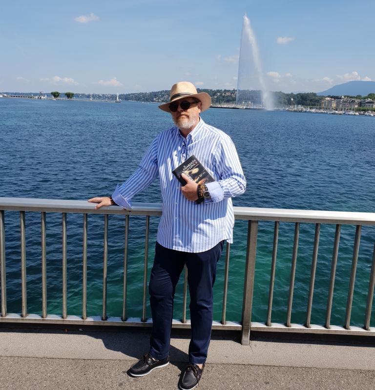 Juan Carlos Cayuso posa con un ejemplar de la Novela EL GUARDIÁN DEL LINAJE, en el lago Leman de Suiza.